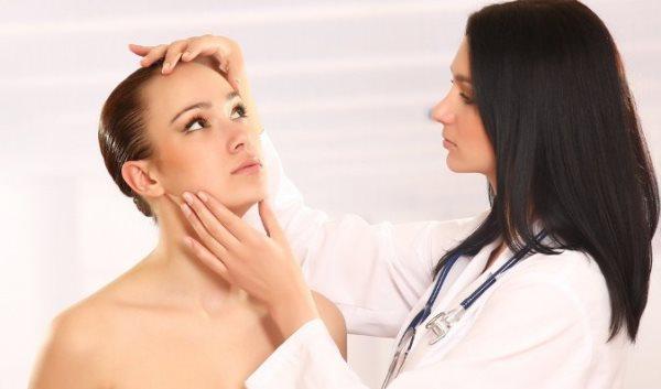 косметолог осматривает лицо