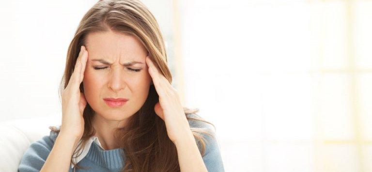 женщина испытывает головную боль