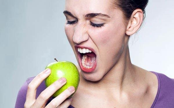 Девушка откусывает яблоко
