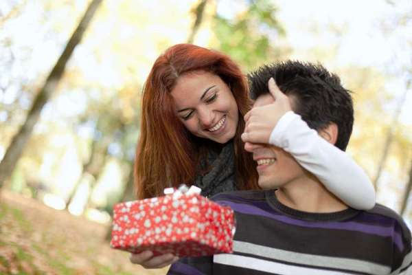 девушка дарит подарок любимому